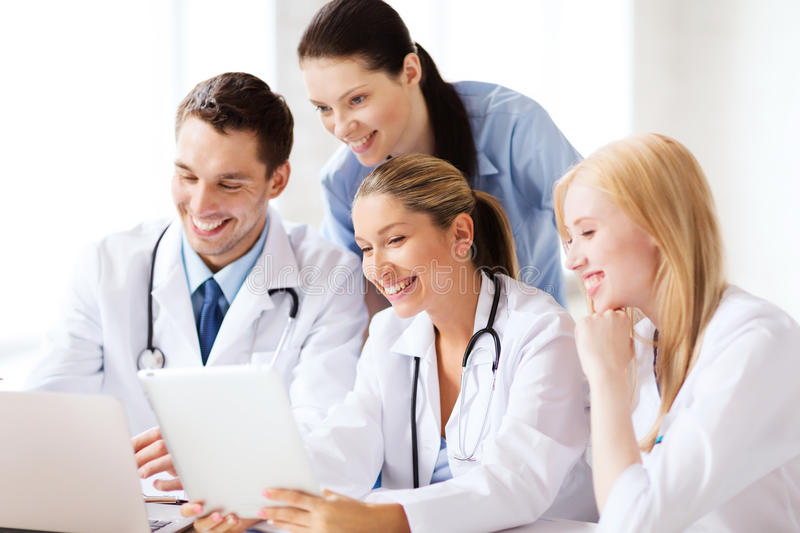 Group of doctors looking at tablet pc. Healthcare, medical and technology concept - group of doctors looking at tablet pc stock photos