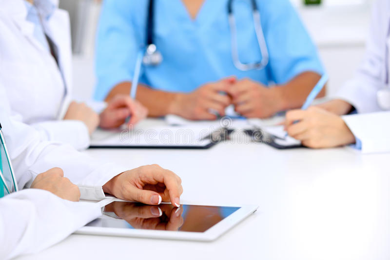 Group of doctors at medical meeting. Close up of physician using tablet computer. Group of doctors at medical meeting. Close up of physician using tablet stock photos