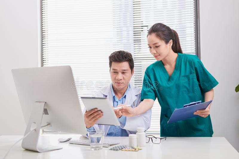 Group of doctors and nurses examining medical report of patient. Team of doctors working together on patients file at hospital royalty free stock photos