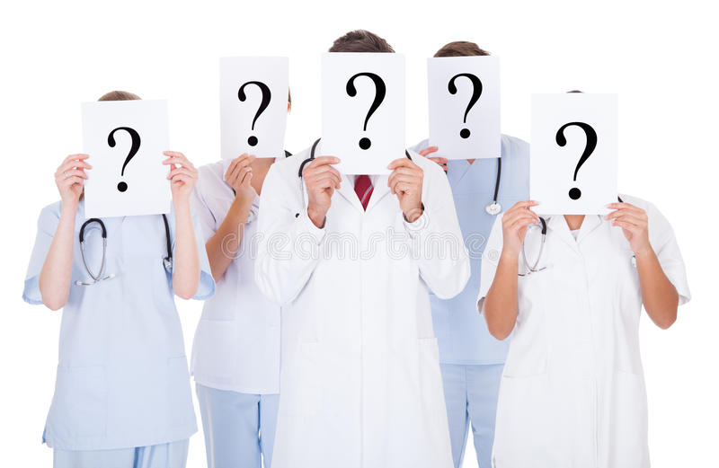 Group of doctors with question mark sign. Group Of Doctors Hiding Face With Question Mark Sign Over White Background royalty free stock images