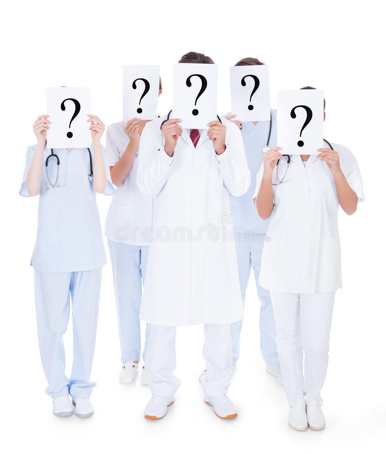 Group of doctors with question mark sign. Group Of Doctors Hiding Face With Question Mark Sign Over White Background stock photo