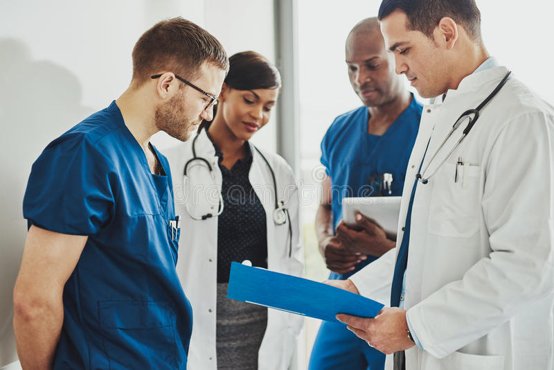 Group of doctors reading a document. In meeting room at hospital stock photos