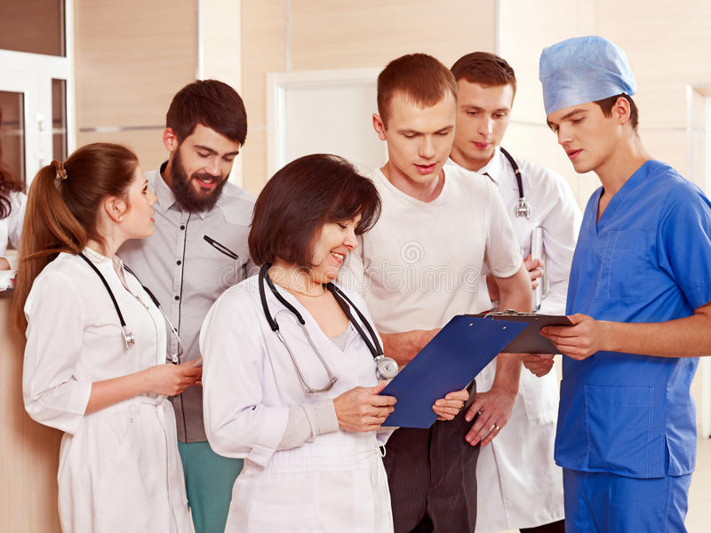 Group doctors at reception in hospital. Group doctors and patient standing at reception in hospital stock photo