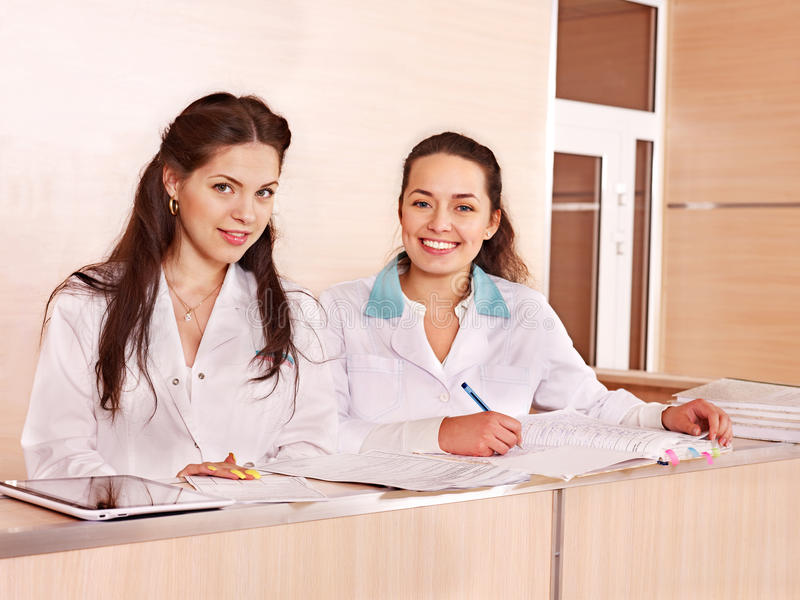 Group doctors at reception in hospital. Group doctors standing at reception in hospital royalty free stock image