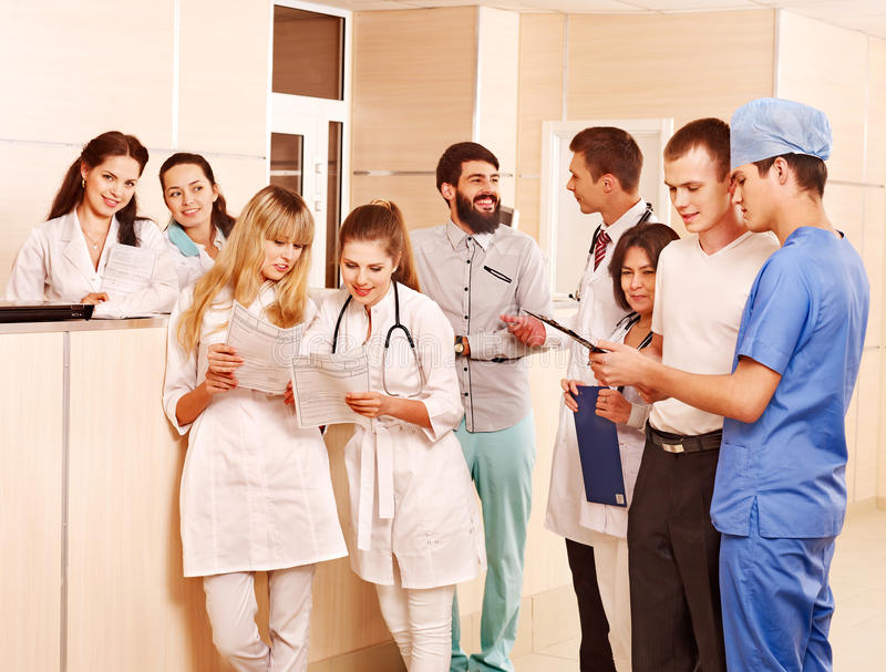 Group doctors at reception in hospital. Large group doctors standing at reception in hospital royalty free stock photography
