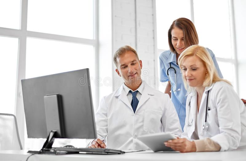 Group of doctors with tablet computer at hospital stock image