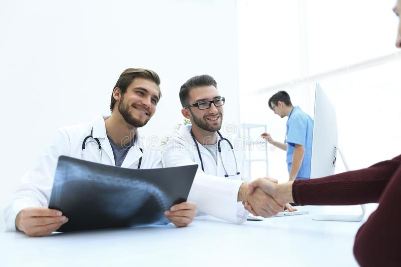 Group of doctors welcoming their customer with a handshake stock photo
