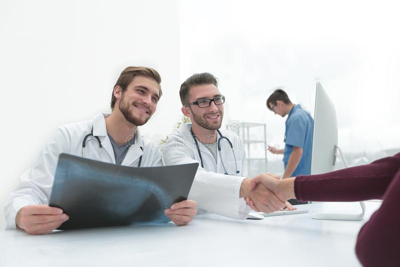 Group of doctors welcoming their customer with a handshake royalty free stock image