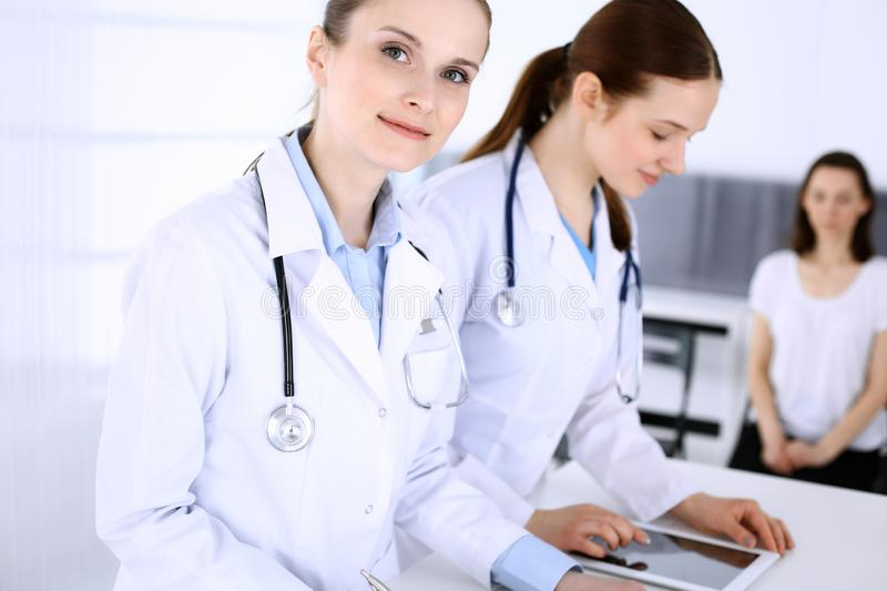 Group of doctors at work in hospital with patient in a queue at the background. Physician filling up medical documents stock photography