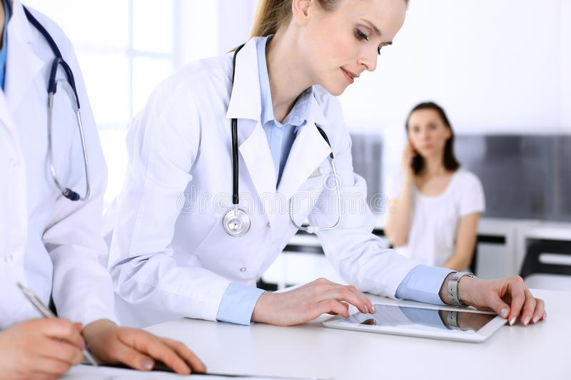 Group of doctors at work in hospital with patient in a queue at the background. Physician filling up medical documents royalty free stock photo