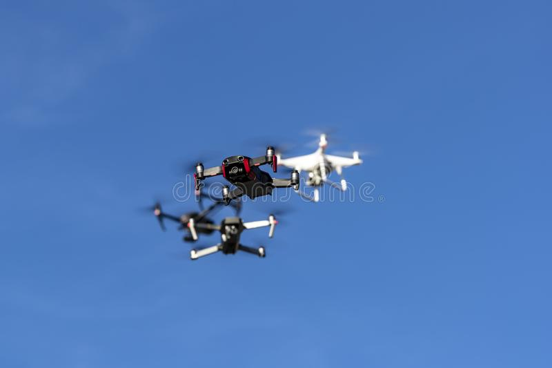 A Group Of Multiple Drones Fly Together Through The Air Against A Blue Sky royalty free stock image