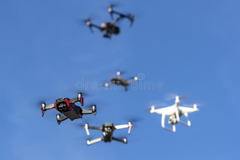 A Group Of Multiple Drones Fly Together Through The Air Against A Blue Sky royalty free stock images