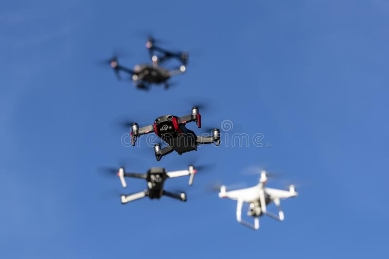 A Group Of Multiple Drones Fly Together Through The Air Against A Blue Sky stock images