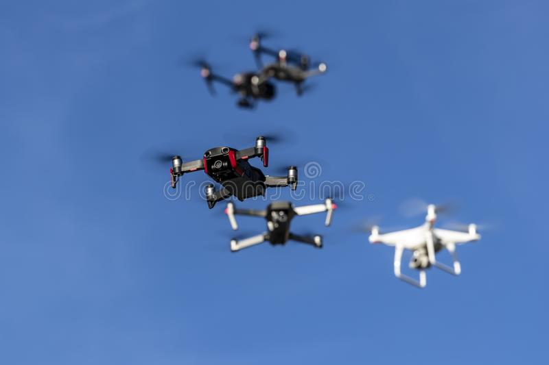 A Group Of Multiple Drones Fly Together Through The Air Against A Blue Sky royalty free stock photos
