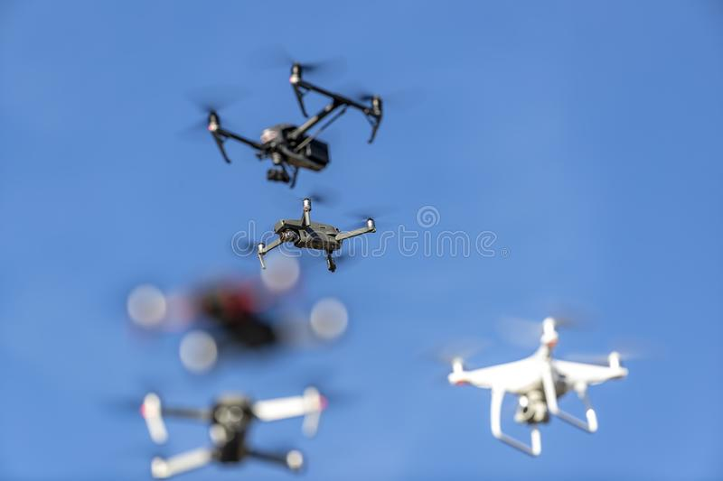 A Group Of Multiple Drones Fly Together Through The Air Against A Blue Sky royalty free stock photography