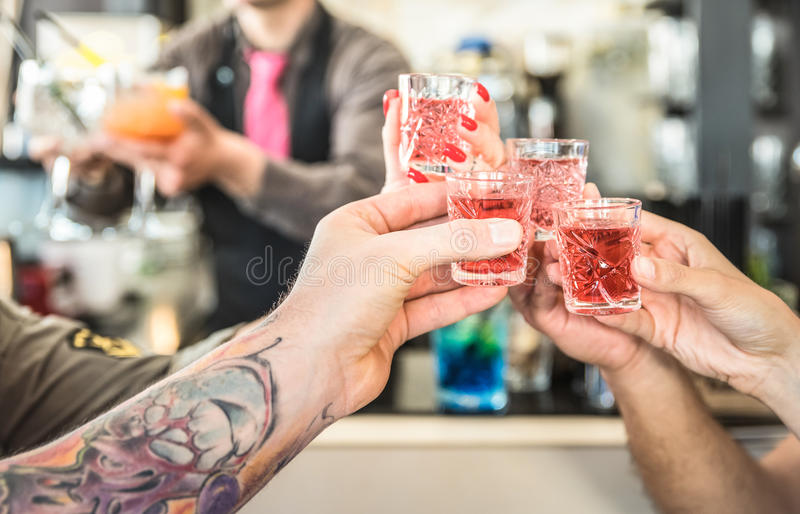 Group of drunk friends toasting cocktails at bar restautant. Food and beverage concept on nightlife moments - Defocused bartender serving drinks on background royalty free stock photos