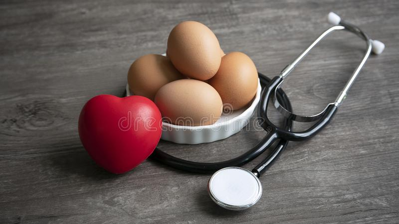 Healthy eating by eggs with stethoscope. Group of eggs with red ball foam with shape heart and stethoscope in healthy eating stock photo