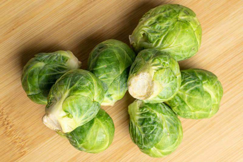 Fresh brussels sprout on light wood. Group of eight whole fresh green brussels sprout flatlay on light wood stock image