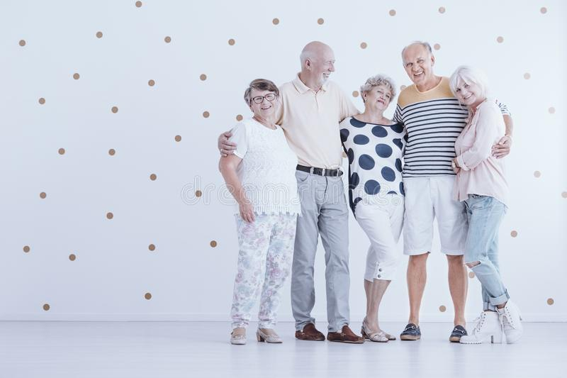 Group of elderly friends hugging each other in white studio with stock photo