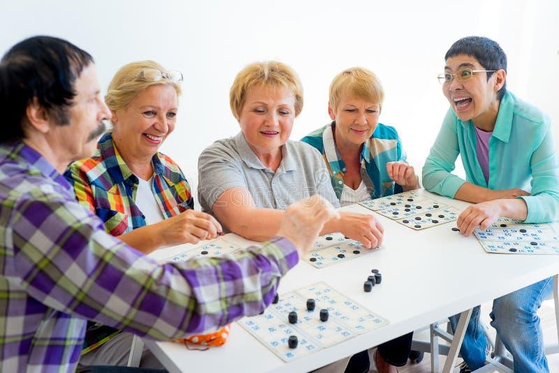 Seniors playing bingo. Group of elderly people playing bingo tigether royalty free stock photo