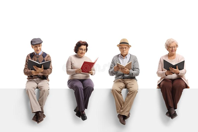 Group of elderly people sitting on a white panel reading books stock image