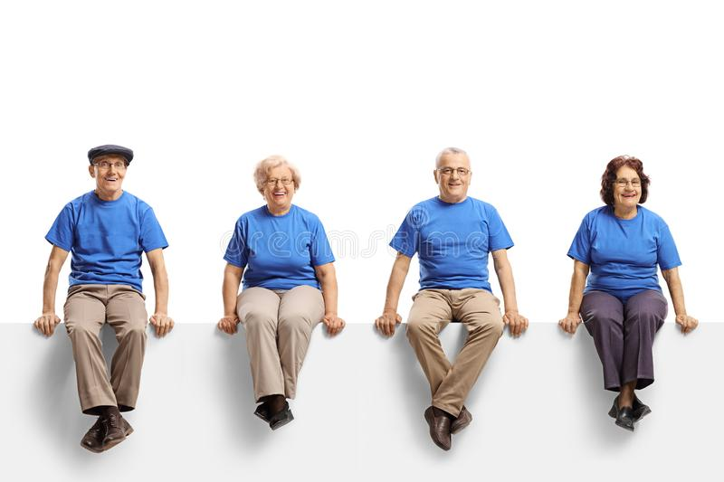 Group of elderly people wearing blue t-shirts sitting on a white panel and smiling at the camera stock photos