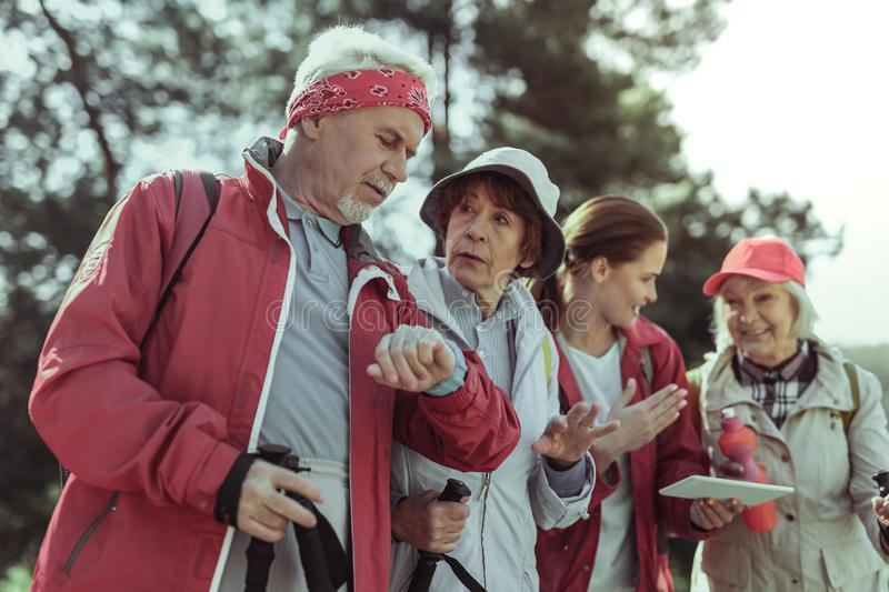 Group of elderly tourists checking time and direction royalty free stock photography