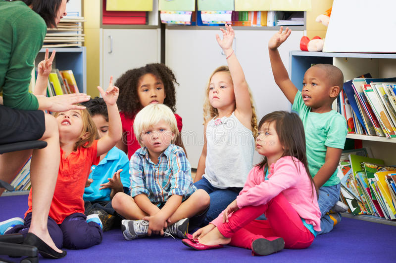 Group of Elementary Pupils In Classroom Answering Question. With Arms Raised royalty free stock photos