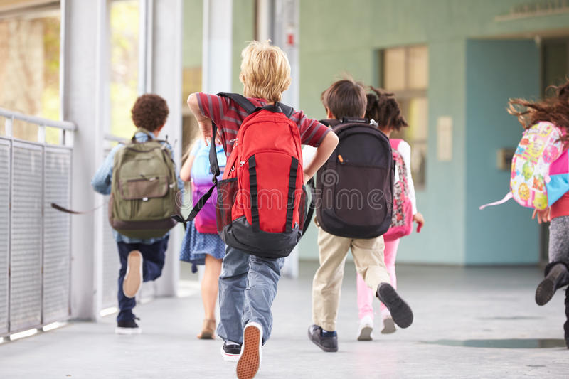 Group of elementary school kids running at school, back view royalty free stock photography