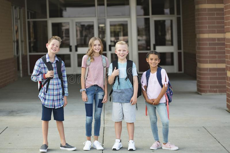 Group of Elementary school students standing in front of their school. Smiling and hanging out together after school. royalty free stock image