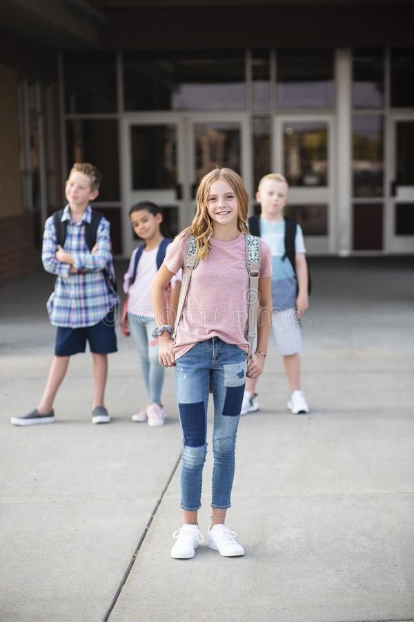 Group of Elementary school students standing in front of their school royalty free stock photography