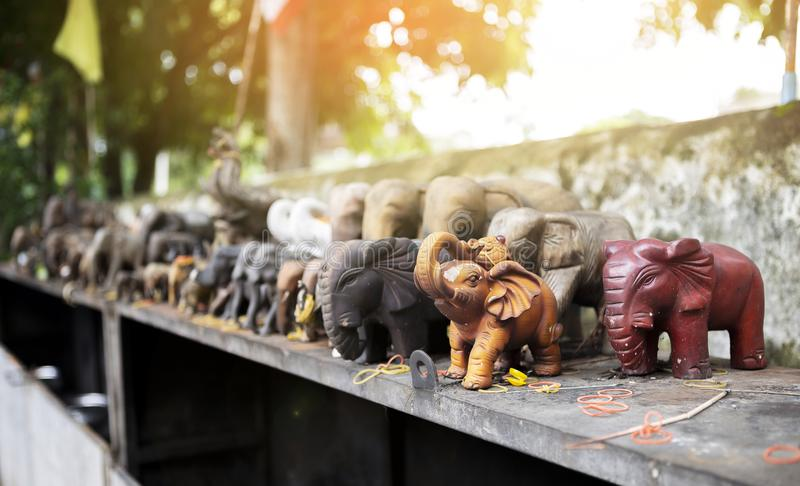 Group of elephant wood craving on the shelf at the temple with vintage warm light stock photography