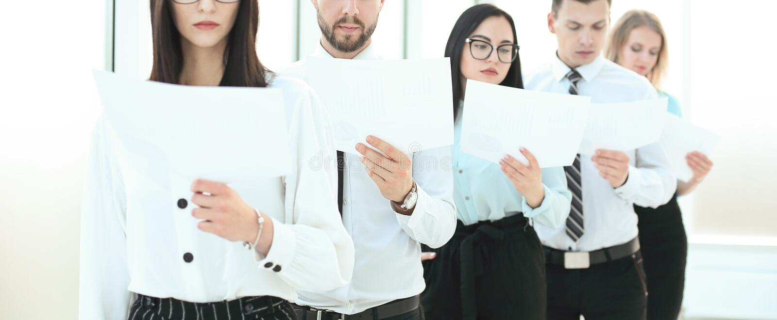 Group of employees with documents standing in a row stock image