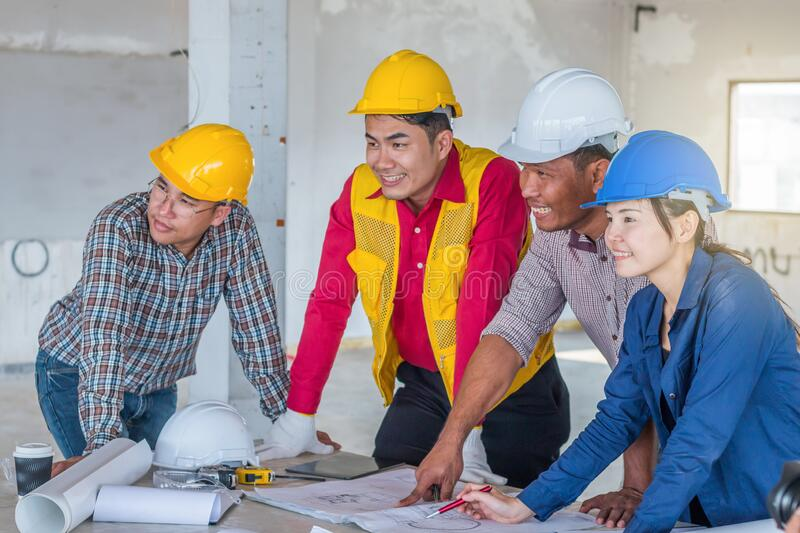 Group of engineer checking the blueprint with laptap and talking about construction project with commitment to success at stock image