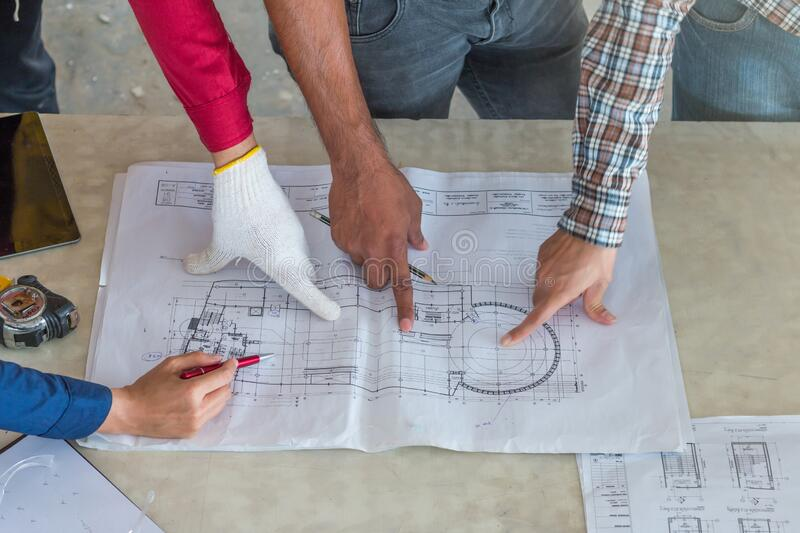 Group of engineer checking the blueprint on table and talking about construction project with commitment to success at royalty free stock image