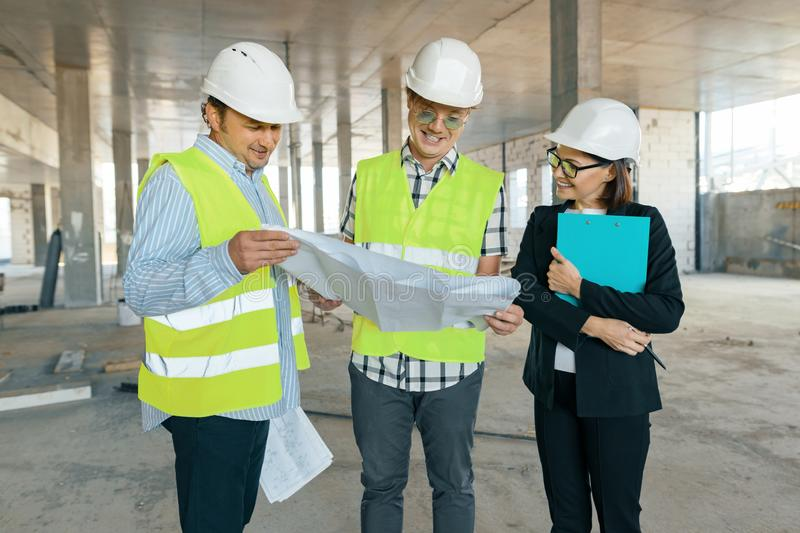 Group of engineers, builders, architects on the building site. Construction, development, teamwork and people concept.  stock images