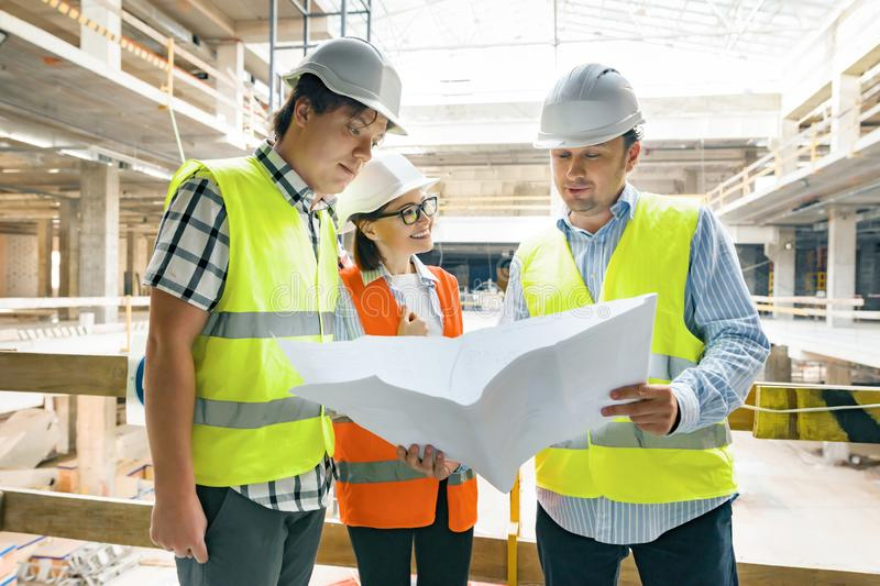 Group of engineers, builders, architects on the building site, looking in blueprint. Construction, development, teamwork and royalty free stock images