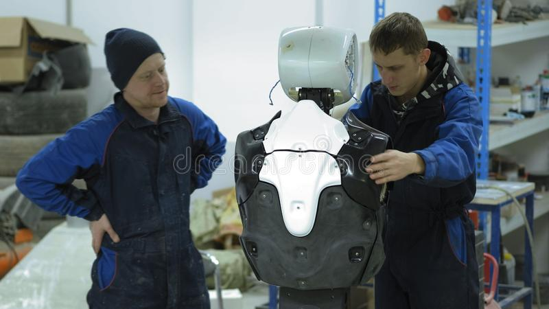 A group of engineers creates a modern robot or android. Check and repair broken items. Manufacture and manufacture of royalty free stock photos