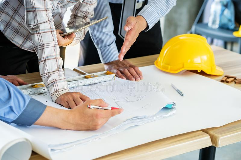 Group of engineers are looking at a blueprint for construction stock image