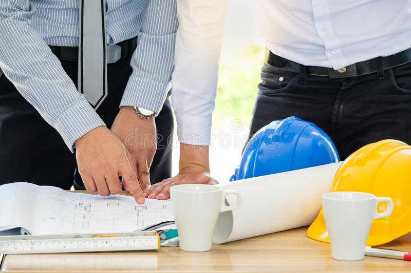 Group of engineers are looking at a blueprint for construction royalty free stock image