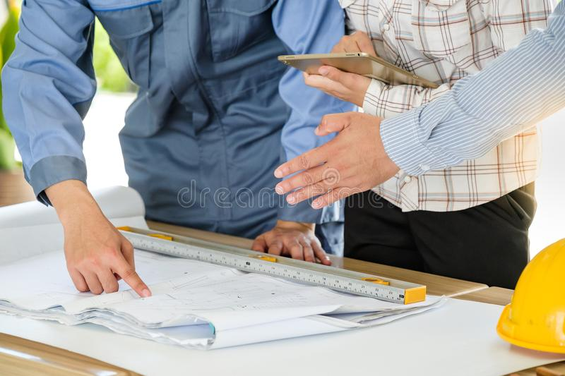 Group of engineers are looking at a blueprint for construction stock photography