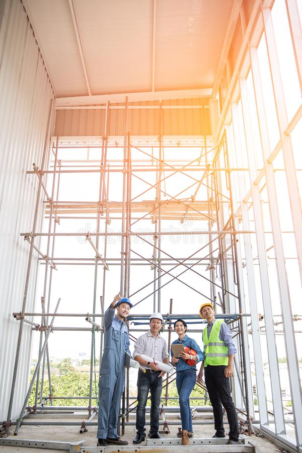 Group of engineers, man and woman, working together in construction site, standing on bridge among the scaffold royalty free stock images