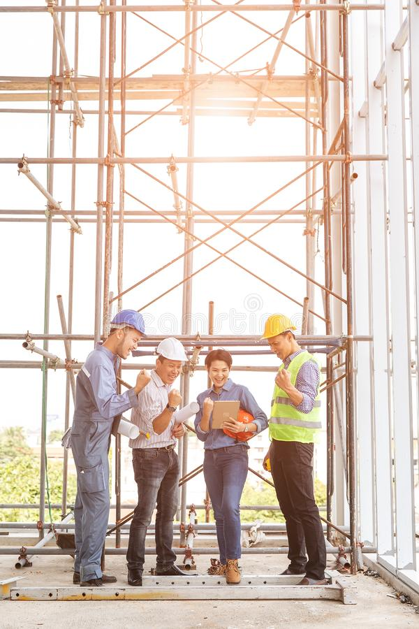 Group of engineers, man and woman, working together in construction site, standing on bridge among the scaffold, orange sun light royalty free stock image
