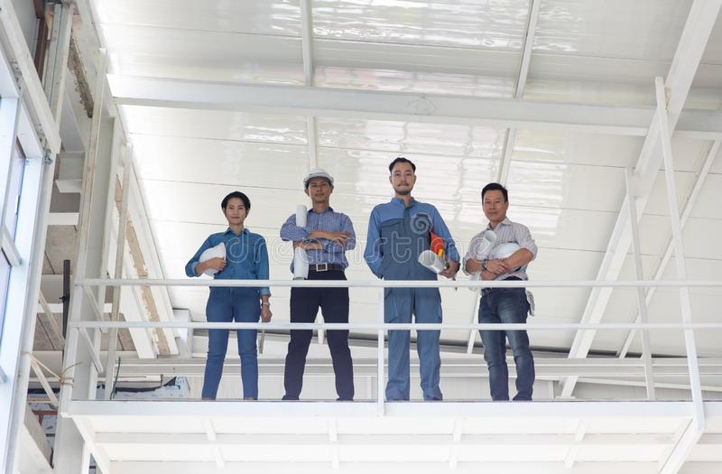 Group of engineers, man and woman, working together in construction site, standing on bridge among the scarfold stock photo