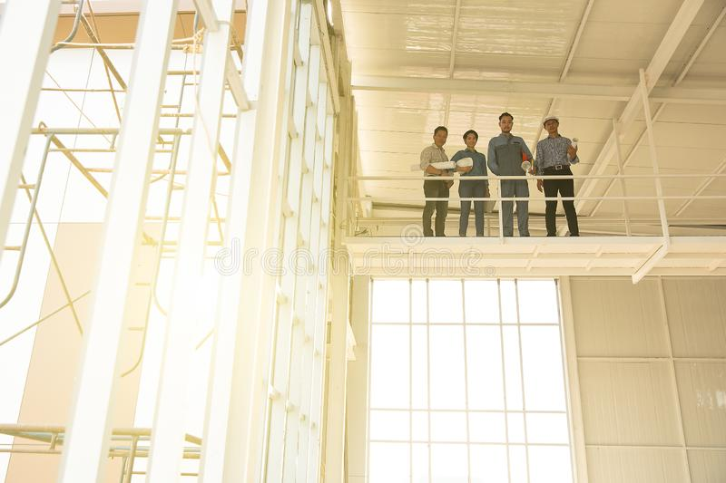 Group of engineers, man and woman, working together in construction site, standing on bridge among the scarfold royalty free stock image