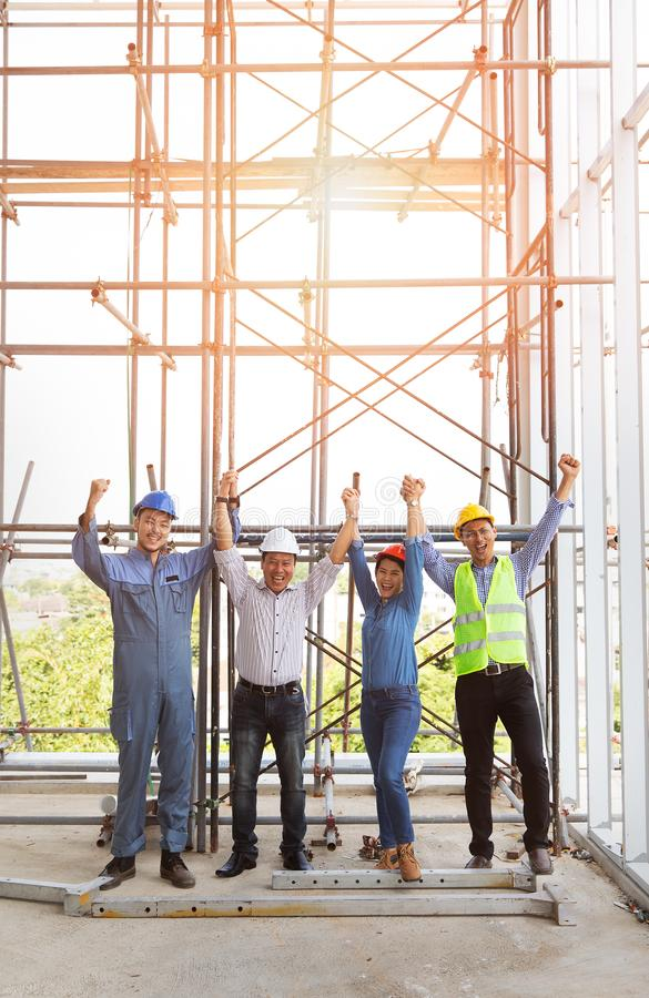 Group of engineers, man and woman, holding and catching hands together in construction site, standing  among the scaffold and pose stock photo
