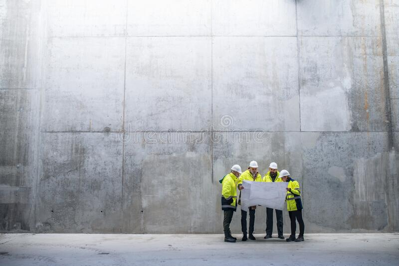A group of engineers standing against concrete wall on construction site. stock images