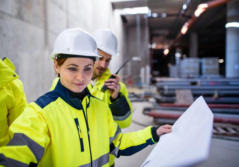 A group of engineers standing on construction site, working. stock images