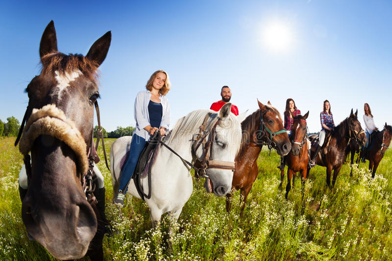 Group of equestrians riding their horses in field. Group of six happy equestrians riding their horses in the summer field stock photo