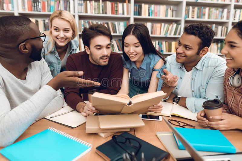 Group of ethnic multicultural students discussing studying in library. royalty free stock photo